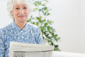 Elderly calm woman reading newspapers — Stock Photo