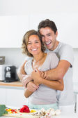 Husband hugging wife at the chopping board — Stock Photo