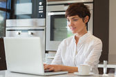 Woman using a computer in kitchen — Stock Photo