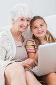 Happy girl using laptop with granny — Stock Photo