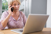 Focused woman using her laptop and calling — Stock Photo