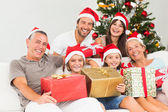 Happy family at christmas holding gifts — Stock Photo