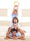 Jolly family having fun with yellow house illustration — Stock Photo