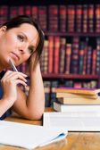 Söt kvinna tänka med pennan och bok — Stockfoto