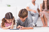 Brother and sister using tablet pc together on floor — Stok fotoğraf