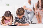 Fratello e sorella utilizzando tablet pc insieme sul pavimento — Foto Stock