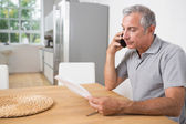 Man calling and reading a sheet of paper — Stock Photo