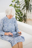 Elderly cheerful woman using a digital tablet — Stock Photo