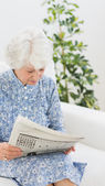 Elderly cheerful woman reading newspapers — Stock Photo