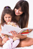 Mother and daughter reading a storybook — Stock Photo