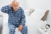 Elderly man suffering with head pain — Stock Photo