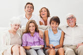Multi-generation family on couch watching tv — Stock Photo