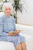 Elderly woman reading a old novel — Stock Photo