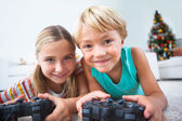 Happy siblings playing video games on floor — Stock Photo