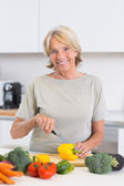 Mature woman cutting a yellow pepper — Stock Photo