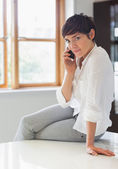 Woman sitting on worktop on the phone — Stock Photo