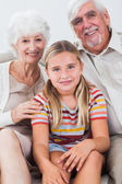 Granddaughter with grandparents on the sofa — Stock Photo