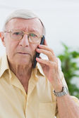 Unhappy elderly man on the mobile phone — Stock Photo