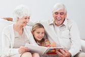 Mutlu küçük kızı dedesi ile okuma — Stok fotoğraf