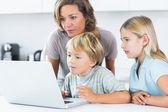 Madre y niños usando laptop — Foto de Stock