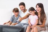 Lyckliga familjen tittar på tv — Stockfoto