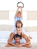 Jolly family having fun with black house illustration — Stock Photo