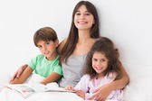 Mother with her children reading a storybook — Stock Photo
