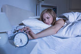 Woman in bed extending hand to alarm clock — Stock Photo
