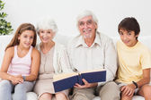 Smiling grandparents with grandchildren reading — Stock Photo