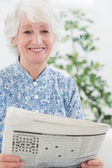 Elderly smiling woman reading newspapers — Stock Photo