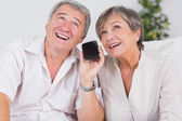 Old couple listening to a smartphone — Stock Photo