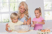 Children mixing dough with their mother — Stock Photo