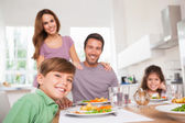Family looking at the camera at dinner time — Stock Photo