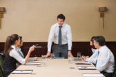 Businessman standing at head of table — Stock Photo
