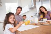 Familia sonriendo a la cámara en el desayuno — Foto de Stock