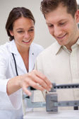 Doctor helping patient with adjusting scale — Stock Photo
