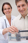 Doctor measuring patients weight — Stock Photo