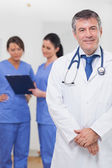Doctor smiling with nurses behind him — Stock Photo