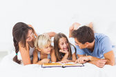 Family reading book on the bed — Stockfoto
