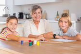 Granny and her grandchildren looking at camera with smile — Stock Photo