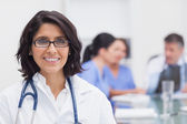 Doctor smiling and her team — Stock Photo