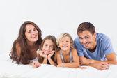 Glückliche familie auf einem bett liegend — Stockfoto