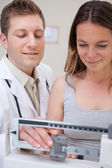 Doctor and patient adjusting scale — Stock Photo