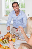 Smiling man carving the turkey — Stock Photo