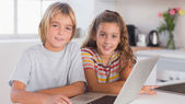 Two children looking at the camera together with laptop in front — Stock Photo