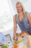 Smiling woman bringing turkey to the table — Stock Photo