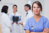 Nurse standing seriously with her team — Stock Photo
