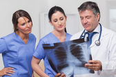 Doctor and nurses looking x-ray — Stock Photo