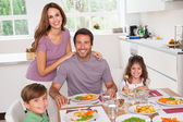 Family smiling at the dinner table — Stock Photo