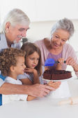 Children icing a cake in the kitchen — Stock Photo